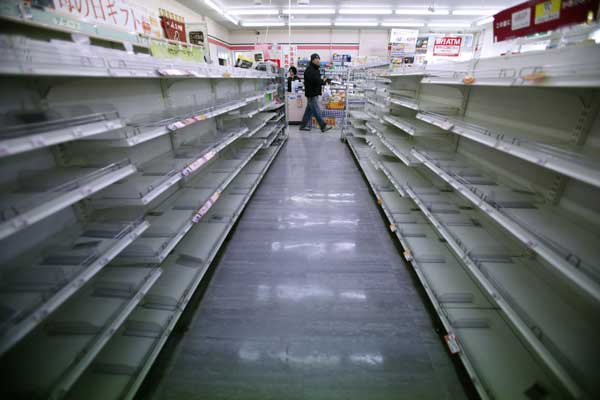 A man shops in a convenience store where shelves on food aisles are left empty in Ofunato, Iwate Prefecture, northern Japan, Tuesday, March 15, 2011, four days after a powerful earthquake-triggered tsunami hit Japan&#39;s east coast.  <span class=meta>(&#40;AP Photo&#47;Shizuo Kambayashi&#41;)</span>